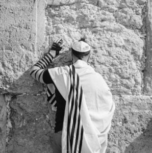 anonymous jewish man in traditional wear praying near old wall